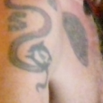 Flea Red Hot Chili peppers arm tattoo of dragon snake dolphin and signature grin and celtic tribal circle disk